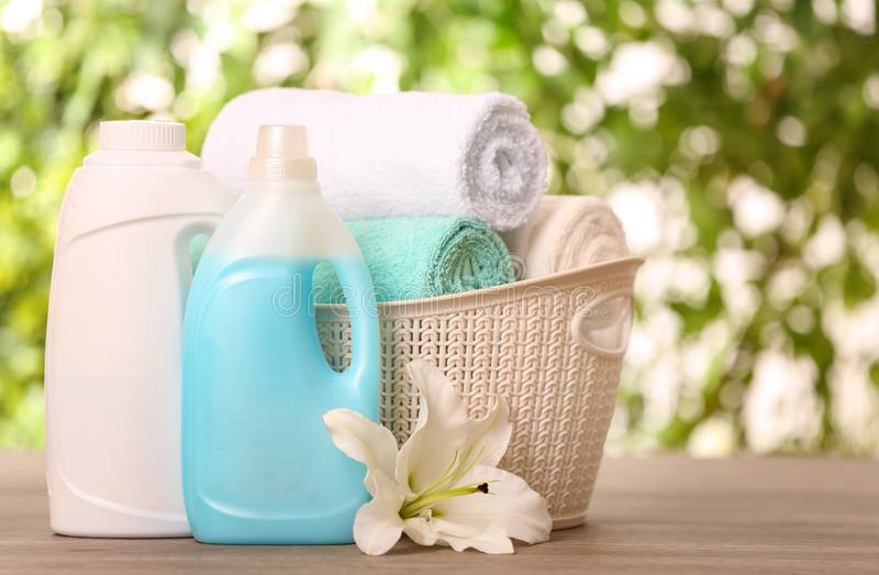 Clean towels in basket with lily and detergents on table against blurred background. Space for text royalty free stock images