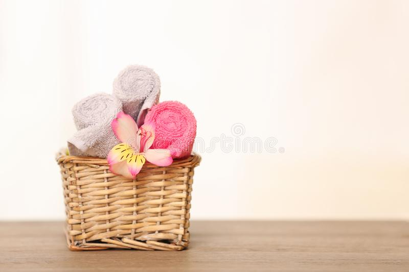 Clean towels with flower in basket on table. Space for text stock photos