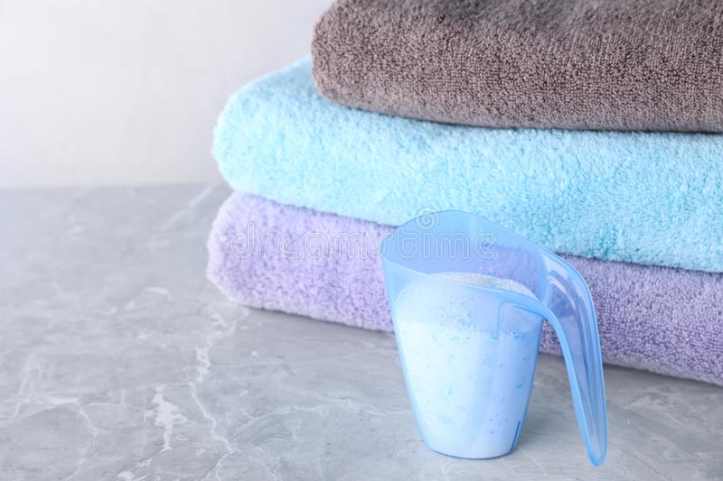 Clean towels and measuring cup of laundry powder on marble table against light background. Space for text royalty free stock photo