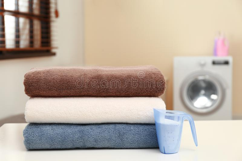 Clean towels and measuring cup of washing powder on table in laundry room. Space for text royalty free stock photography