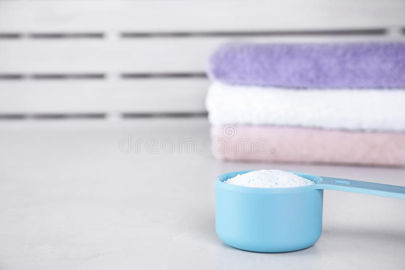 Clean towels and measuring scoop of washing powder on table. Space for text stock image