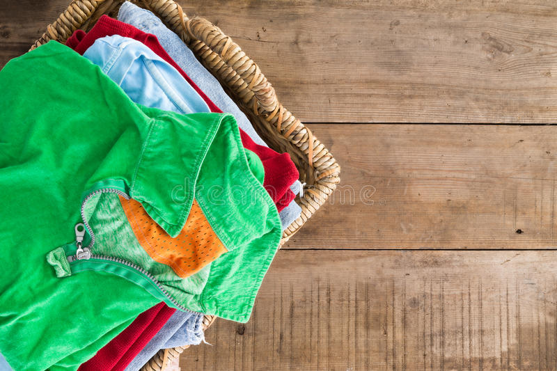 Clean unironed summer clothes in a laundry basket. Clean washed unironed summer clothes with a fresh fragrance stacked in a wicker laundry basket with a bright royalty free stock photography