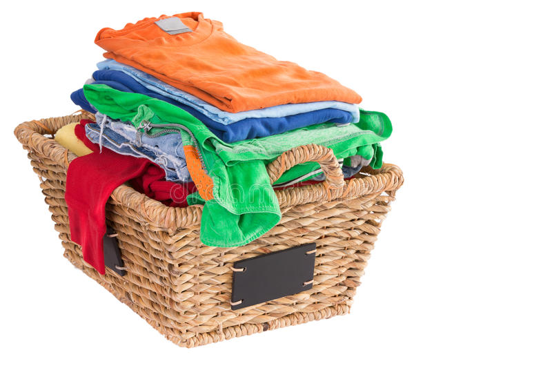 Clean washed fresh summer clothes in a basket. Colorful collection of clean washed fresh summer clothes in a rustic woven wicker laundry basket with blank royalty free stock photography