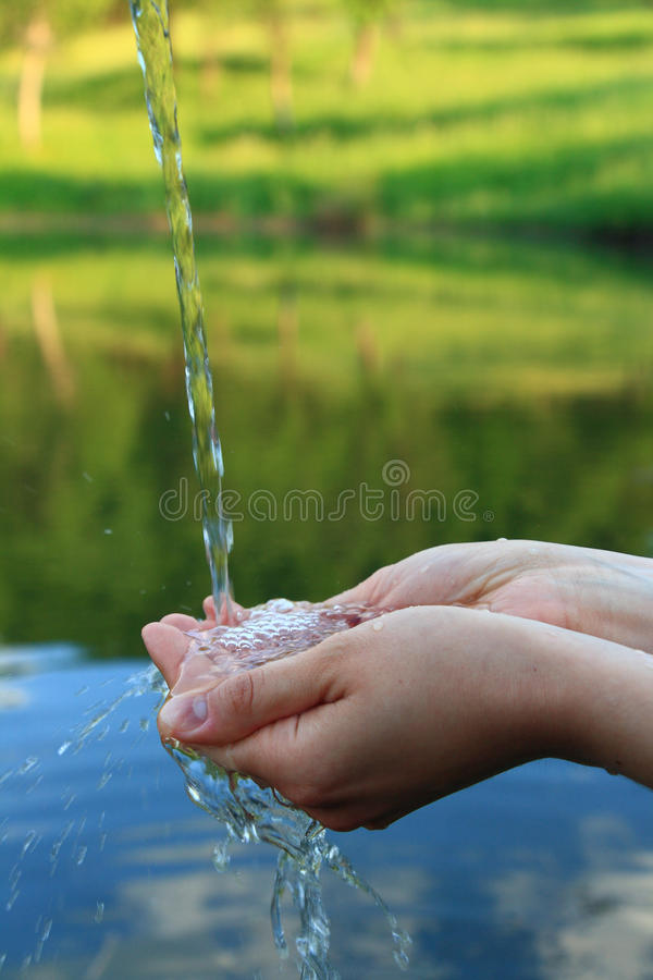 Hands in clear water against mountain lake royalty free stock image