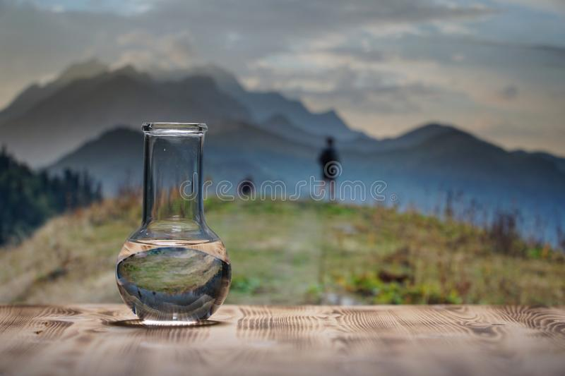 Clean water in a glass laboratory flask on wooden table on mountain background. Ecological concept, the test of purity. Clean water in a glass laboratory flask stock photos