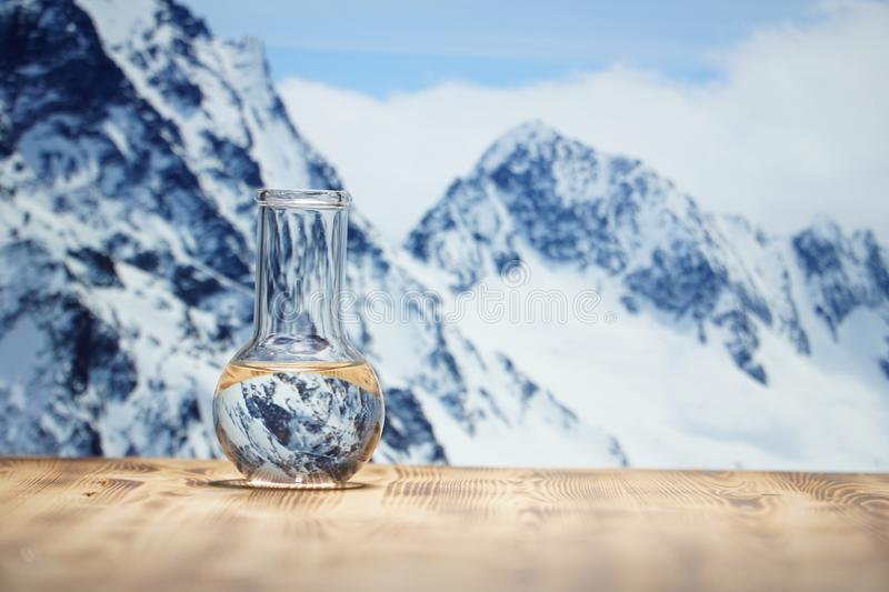 Clean water in a glass laboratory flask on wooden table on winter mountain background. Ecological concept, the test of. Clean water in a glass laboratory flask royalty free stock images