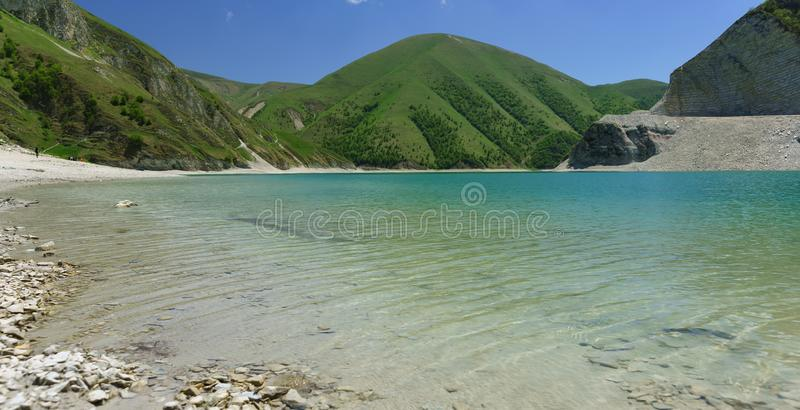 Clean water of the high-mountain lake Kezenoi am in Botlikh district of the Republic of Dagestan. Lush greenery covers the slopes. Of the mountains in early stock photography