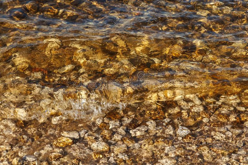 Clean water of river waves near the shore with a rocky bottom. Abstract background textures, rocks and sand in the river stock photos
