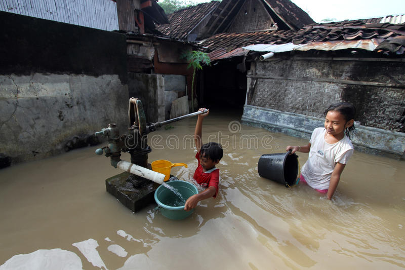 Clean water. Two children looking for a clean water the time of floods in Solo royalty free stock photo