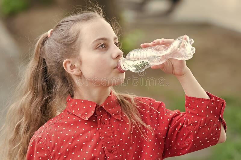 Clean water is a vital resource for human existence. Little girl having a drop of water. Thirsty child drinking fresh stock photos
