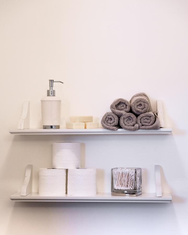 Clean white bathroom shelving with towels toilet paper soap and lots of empty space. stock image