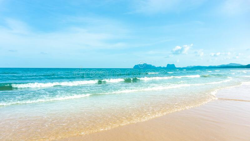 Clean white beach golden brown sand and blue sea under clear blue sky in a sunny day, mountain on background. S stock photos
