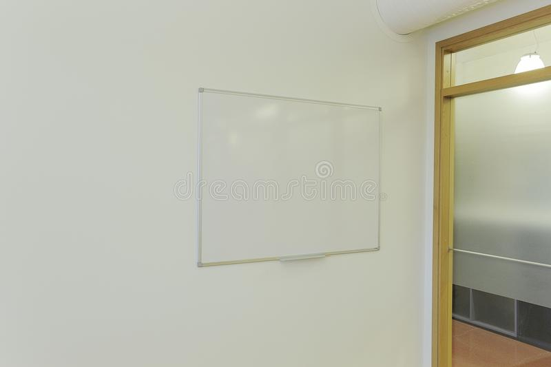 Clean white board on white wall in office room. Meeting room. Conference room. stock image