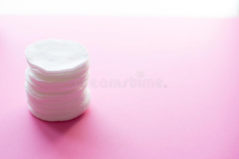 Clean white cotton stack of disk for beauty face hygiene with selective focus on pink neutral background. Cosmetic softness pure stock photography