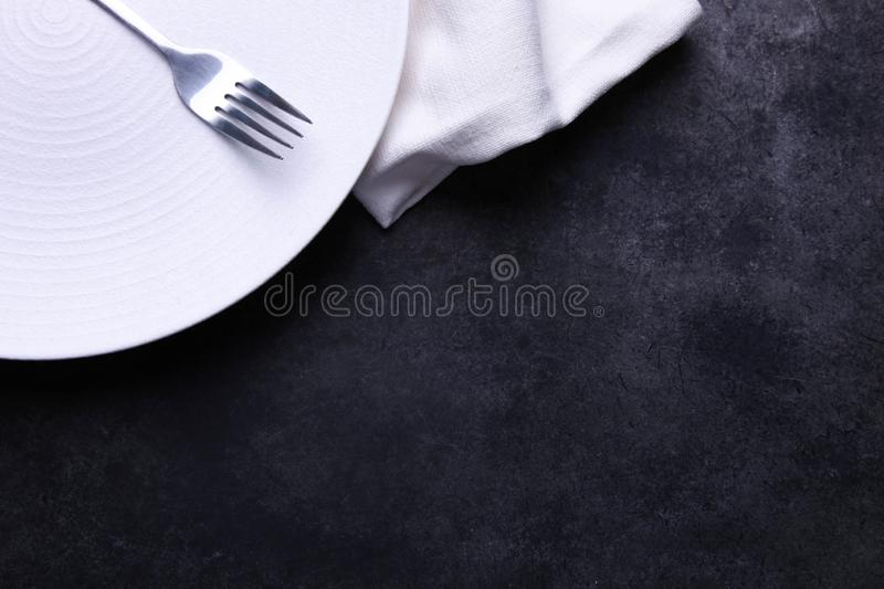 Clean white plate, fork and napkin. On black background. Concept table setting. Top view, copy space royalty free stock photography