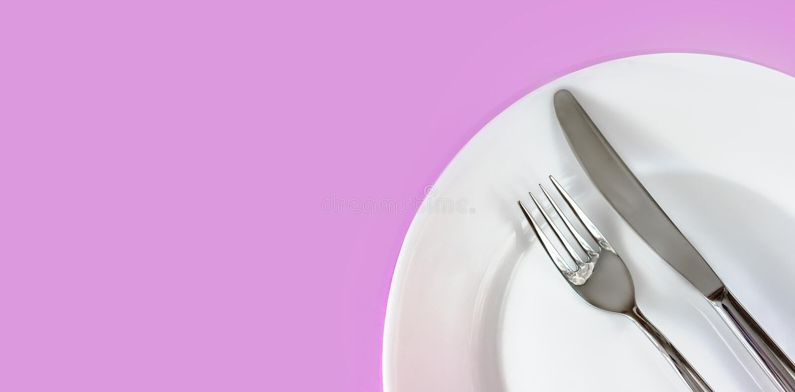 Clean white plate and stainless knife and fork  on light purple background. Served cutlery. Time to eat. Top view. Copy space stock images