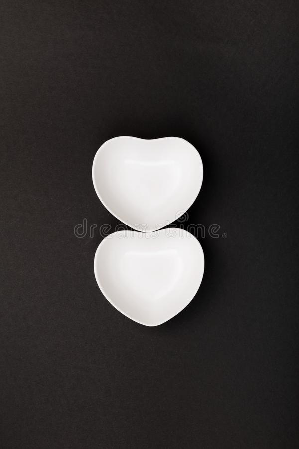 Clean white tableware in form of heart on black background. Top view.  stock images