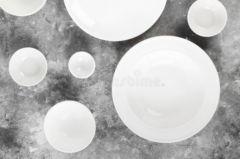 Clean white tableware on a gray background. Top view stock image