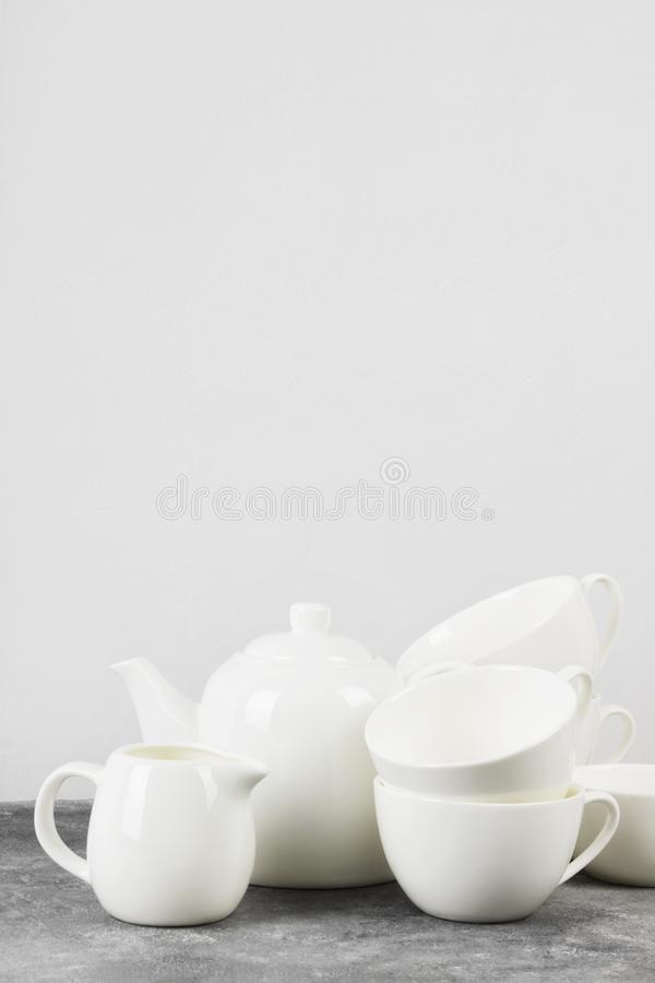 Clean white tableware teapot, cups, saucers on a gray backgrou royalty free stock photos