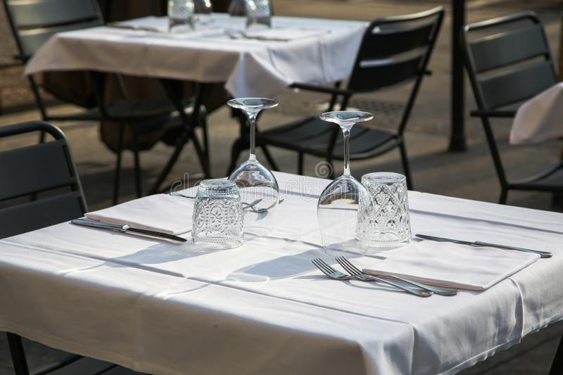 Street cafe table laid for guests with natural lighting. Clean wine glasses, knives and forks lie on the table set to receive guests in natural light royalty free stock photo