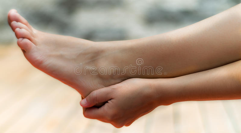 Clean woman foot and her right hand touching her heel, background of wood and stone.  royalty free stock photos
