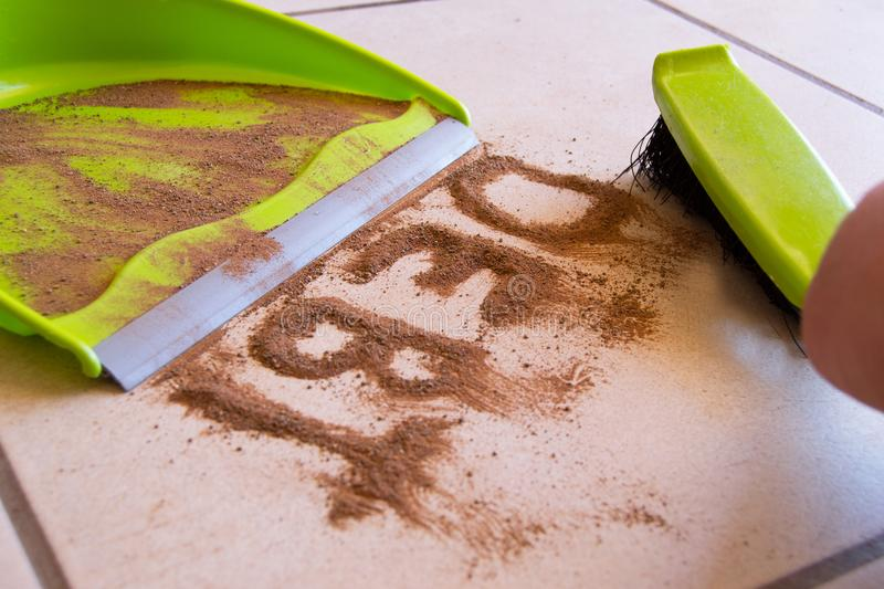 Clean Your Debt. Concept with debt written in dirt on a floor and a person is about to sweep the debt dirt in a dust pan using a small hand broom royalty free stock images
