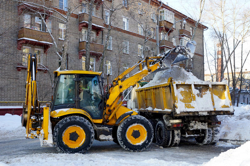 Cleaned snow. The tractor loads the cleaned snow on the dump truck royalty free stock photo