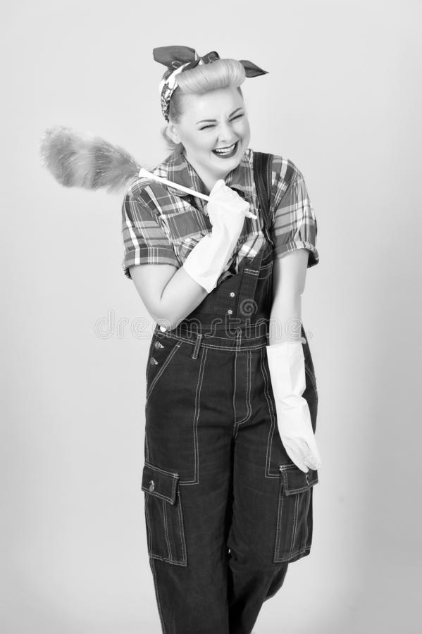 Cleaner blonde girl in denim with duster and happy shutdown eyes. Blonde girl in retro american style with curls and scurf on head stock photography