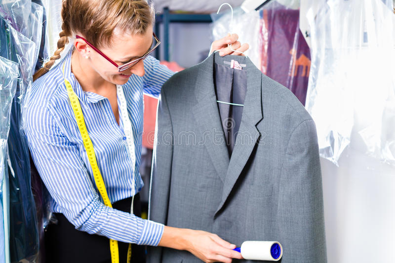 Cleaner in laundry shop checking clean clothes. Female cleaner in laundry shop checking clean clothes removing lint with roller stock photography