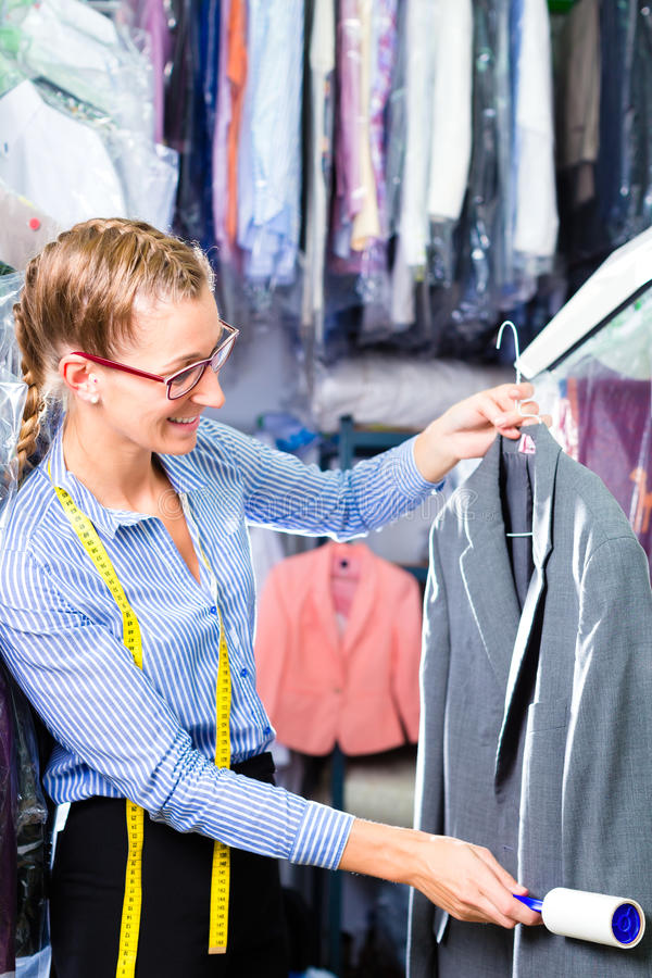 Cleaner in laundry shop checking clean clothes. Female cleaner in laundry shop checking clean clothes removing lint with roller stock image