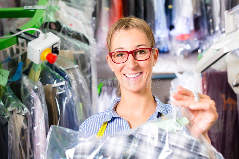 Cleaner in laundry shop checking clean clothes. Female cleaner in laundry shop or textile dry-cleaning next to clean clothes in garment bags stock photo