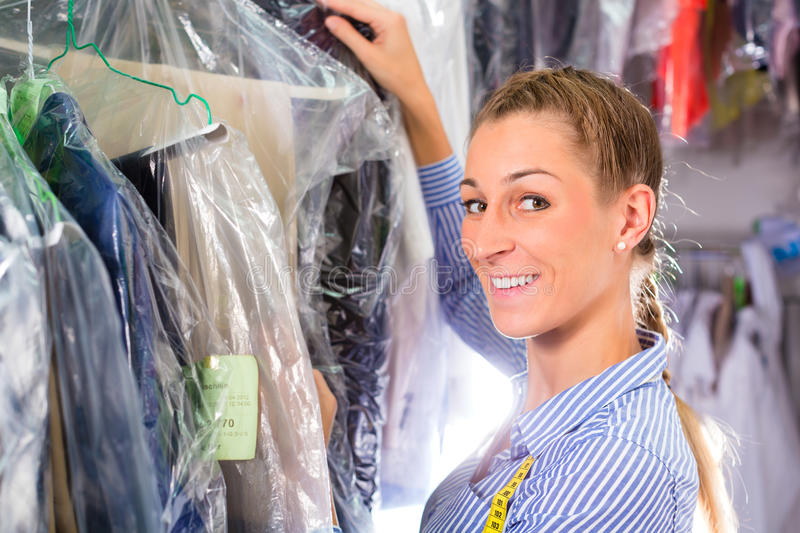 Cleaner in laundry shop checking clean clothes. Female cleaner in laundry shop or textile dry-cleaning next to clean clothes in garment bags stock photos