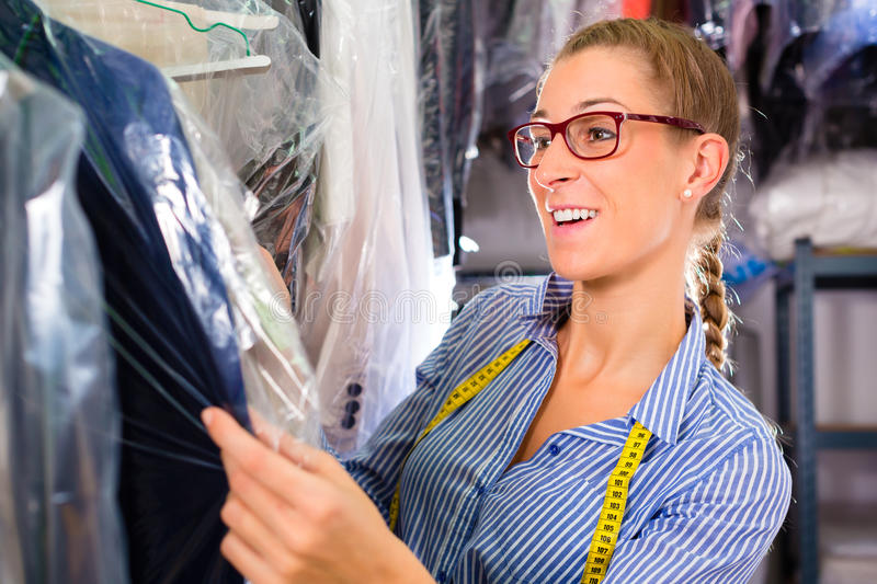 Cleaner in laundry shop checking clean clothes. Female cleaner in laundry shop or textile dry-cleaning next to clean clothes in garment bags royalty free stock image