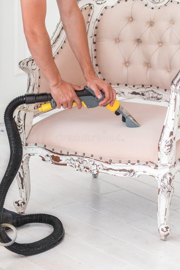 Cleaner& seco x27; a mão do empregado de s está limpando o sofá clássico com profissionalmente o método da extração foto de stock royalty free