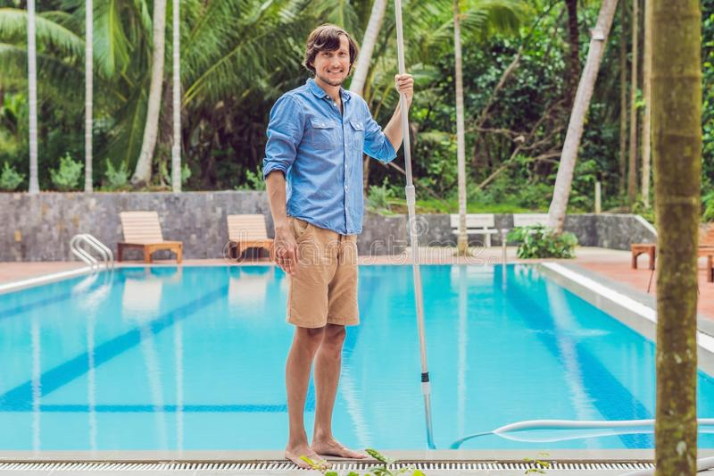 Cleaner of the swimming pool . Man in a blue shirt with cleaning royalty free stock photography
