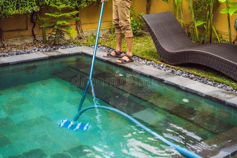 Cleaner of the swimming pool . Man in a blue shirt with cleaning equipment for swimming pools. Pool cleaning services stock photo