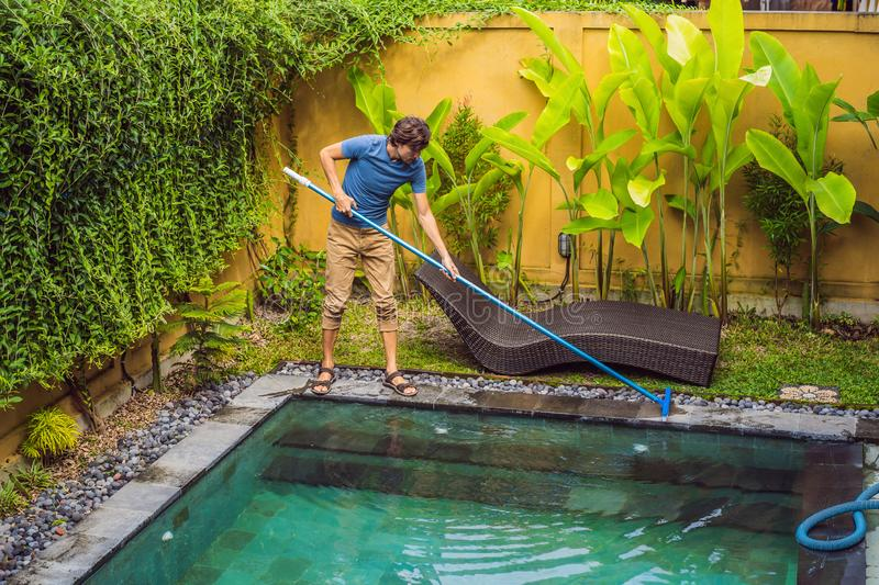 Cleaner of the swimming pool . Man in a blue shirt with cleaning equipment for swimming pools. Pool cleaning services stock image