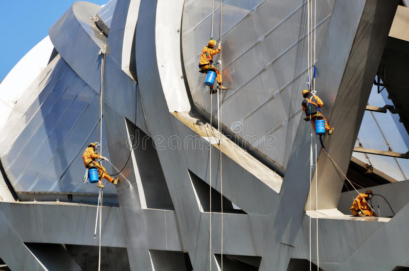 Cleaners being working aloft. Some cleaners was working aloft in the high-rise buildings which is the China's Olympic center stock image