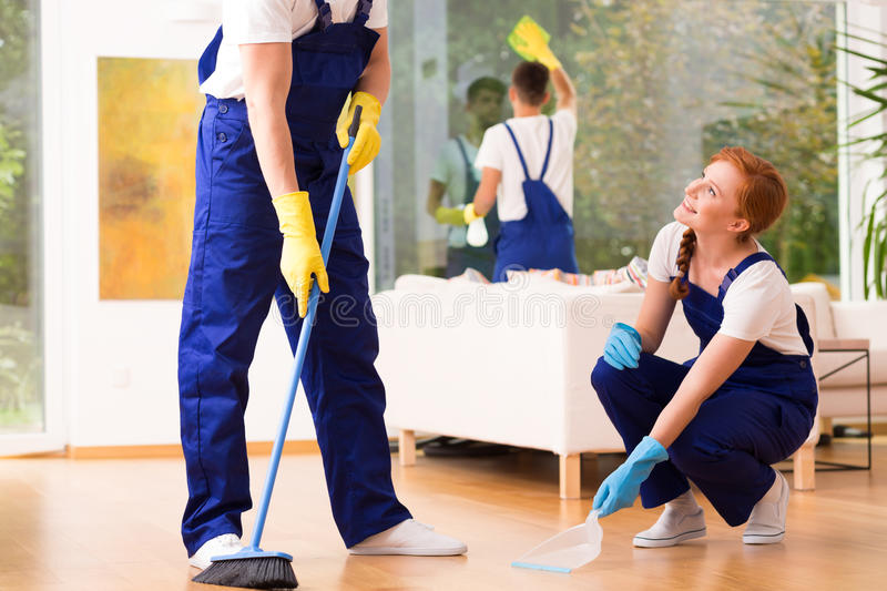 Cleaners sweeping floor. Professional cleaners wearing uniforms, sweeping floor royalty free stock photos