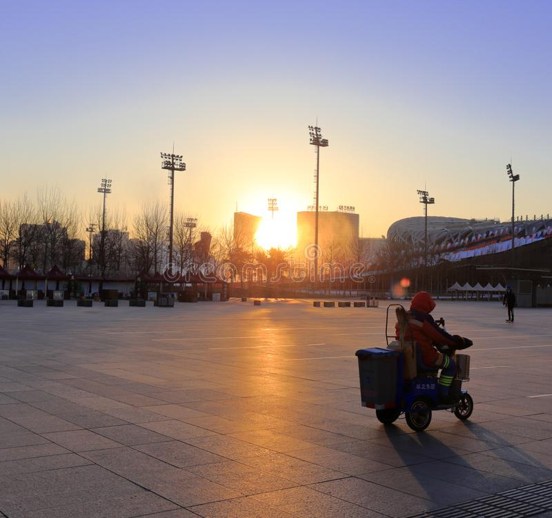 Cleaners work at beijing olympic sports center plaza at sunrise, adobe rgb stock photography