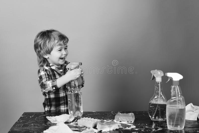 Cleaning activities concept. Kid with laughing face spraying water out of spray bottle. royalty free stock image