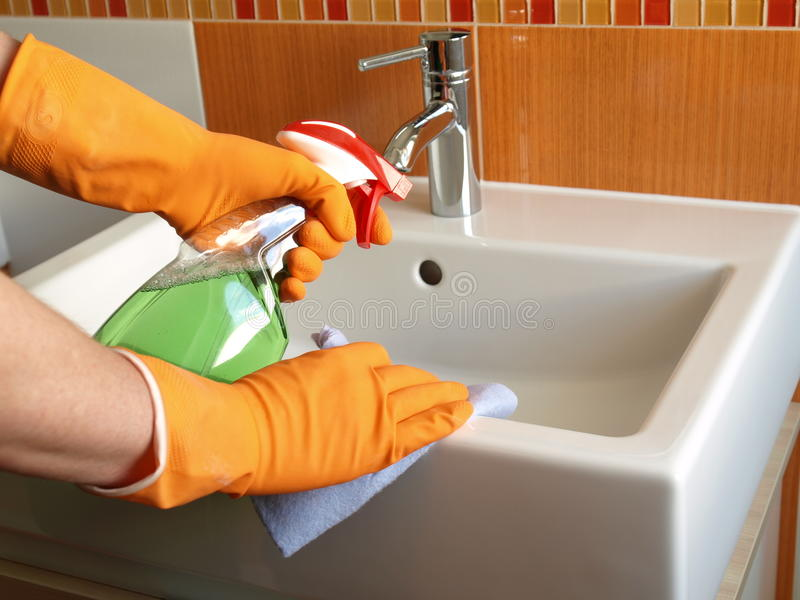 Cleaning bathroom sink. House keeping: cleaning bathroom sink with spray stock images