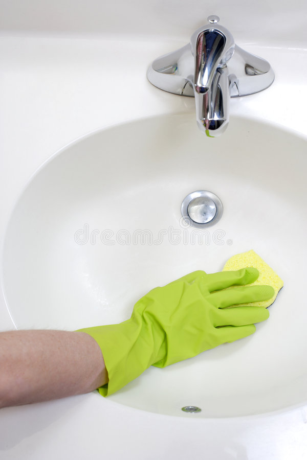 Cleaning Bathroom Sink. A person cleaning the bathroom sink with a glove stock images