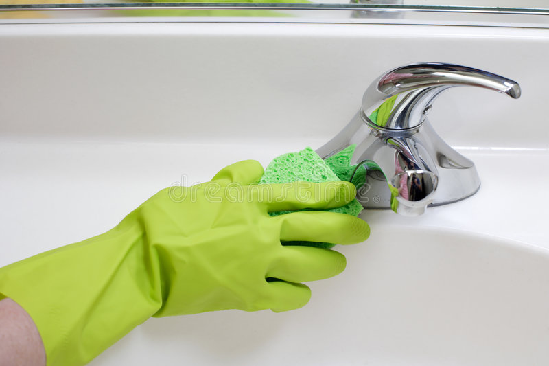 Cleaning Bathroom Sink. A person cleaning the bathroom sink with a glove stock image