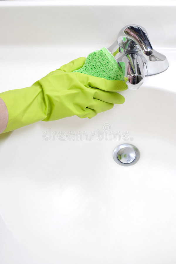 Cleaning Bathroom Sink. A person cleaning the bathroom sink with a glove royalty free stock photos