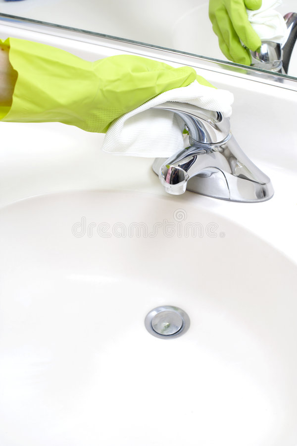 Cleaning Bathroom Sink. A person cleaning the bathroom sink with a glove royalty free stock photo