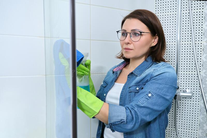 Cleaning bathroom, woman washing and polishing shower glass stock photos