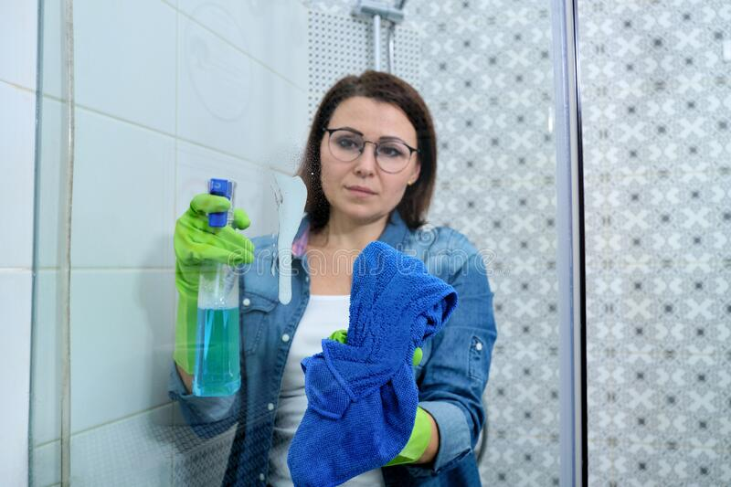 Cleaning bathroom, woman washing and polishing shower glass stock photography