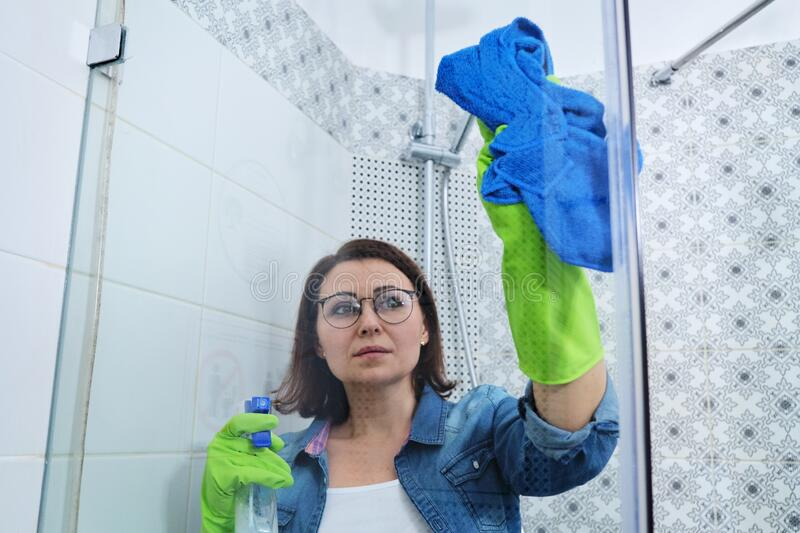 Cleaning bathroom, woman washing and polishing shower glass royalty free stock image