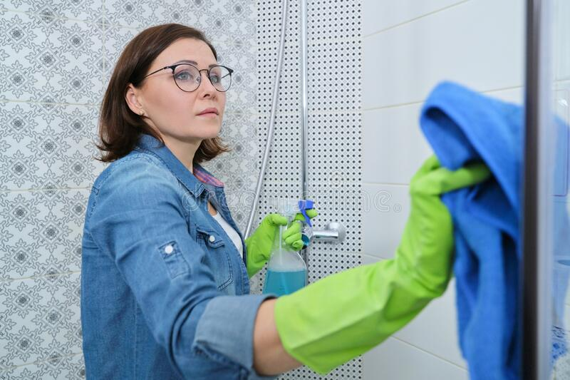 Cleaning bathroom, woman washing and polishing shower glass stock image